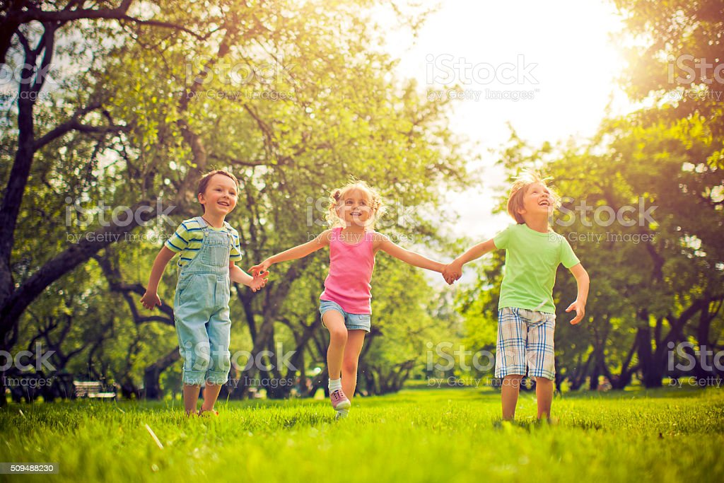 Three happy children in summer stock photo