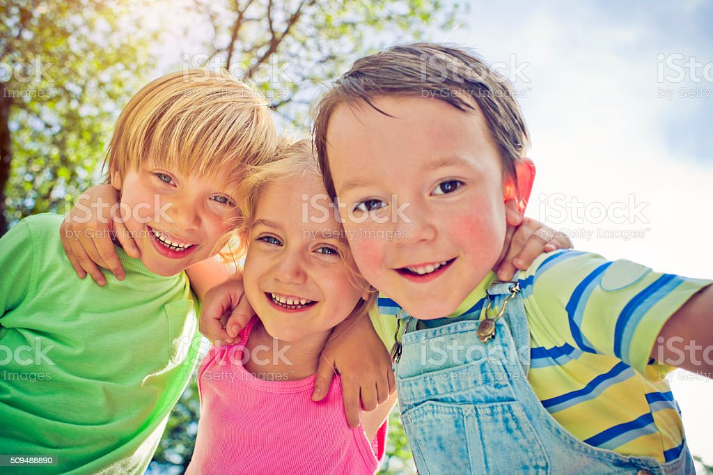 Three happy children in summer stock photo