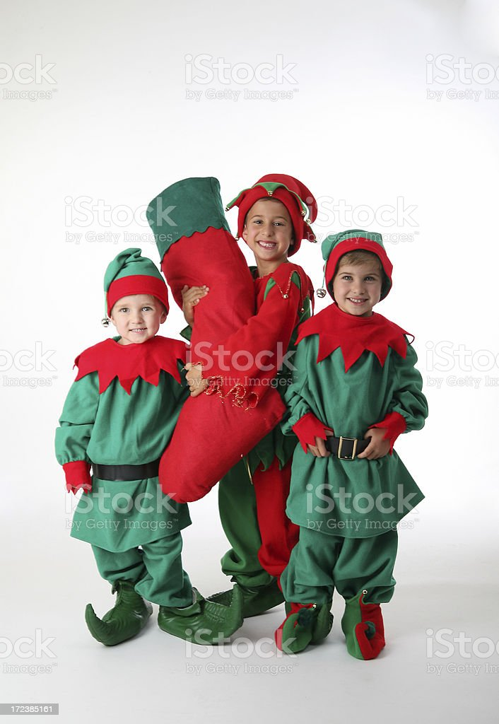 three happy elves with stocking stock photo