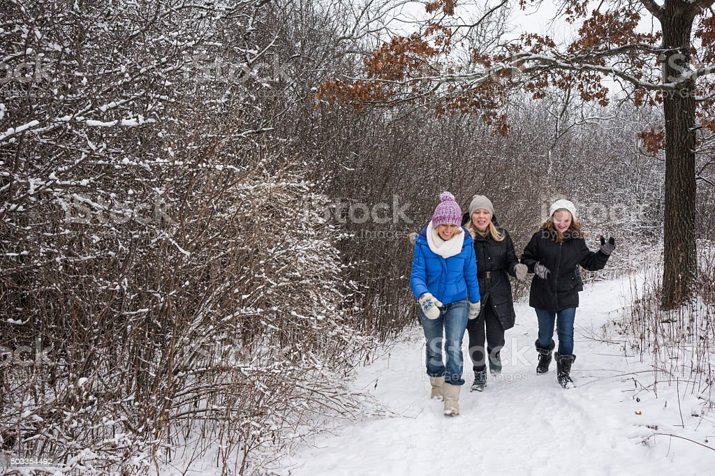 Three happy females hiking in winter forest stock photo