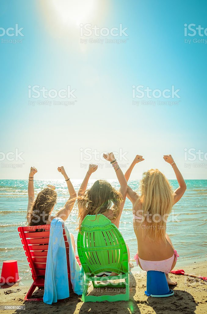 Three happy friends on the beach for summer stock photo