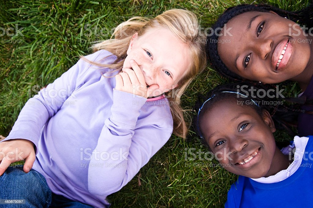 Three Happy Girls Laughing in the Grass royalty-free stock photo