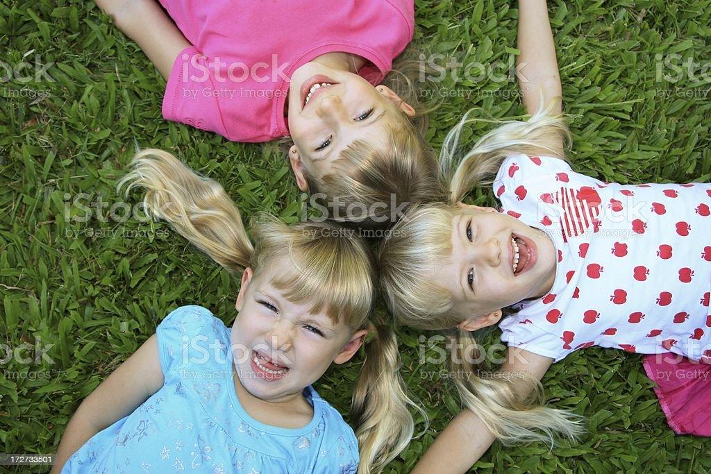 Three Happy Girls on green grass royalty-free stock photo