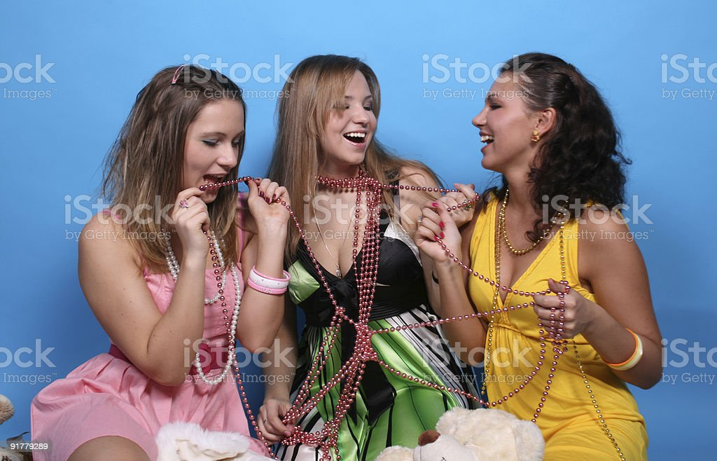 Three happy girls with beads and toys royalty-free stock photo