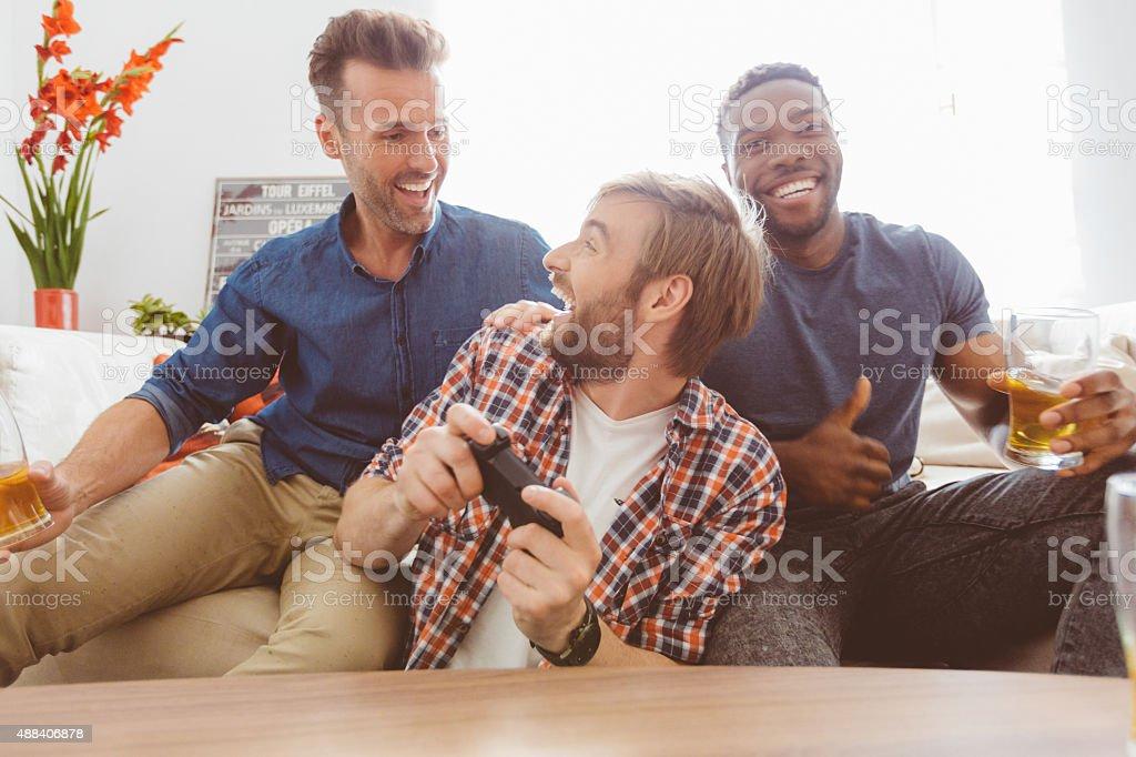 Three happy guys playing video games stock photo