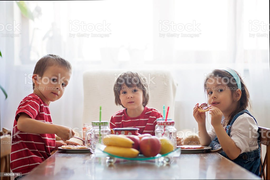 Three happy kids, two brothers and little sister, having healthy stock photo