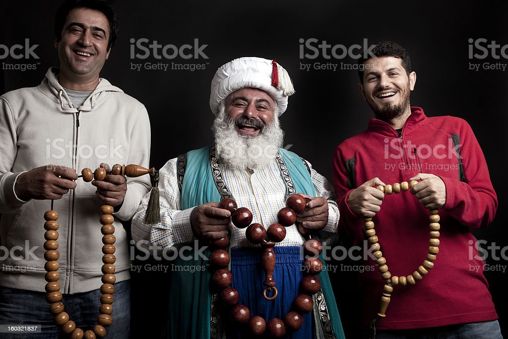Three happy men holding wooden beads stock photo