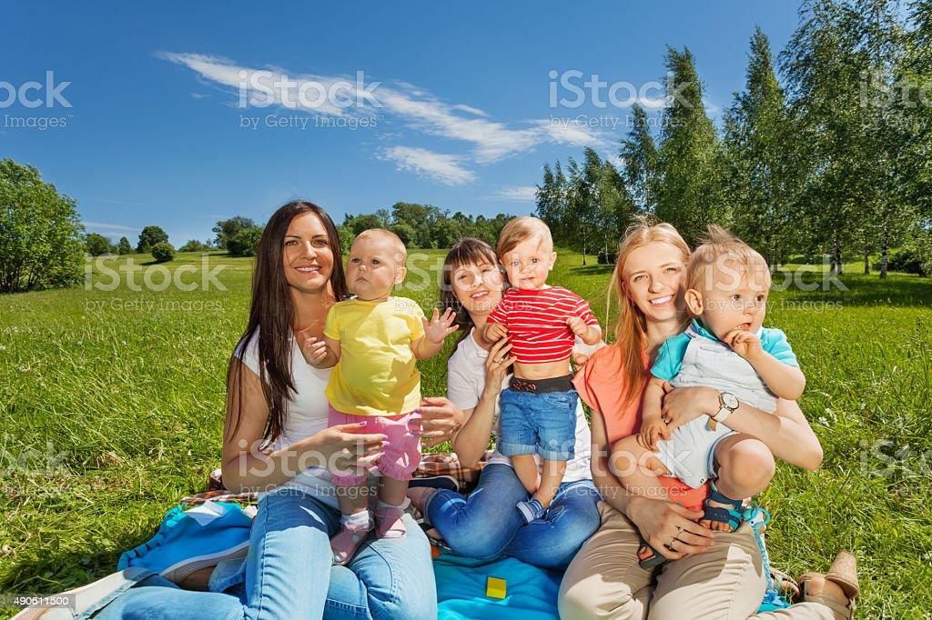 Three happy mothers holding cute babies in park stock photo