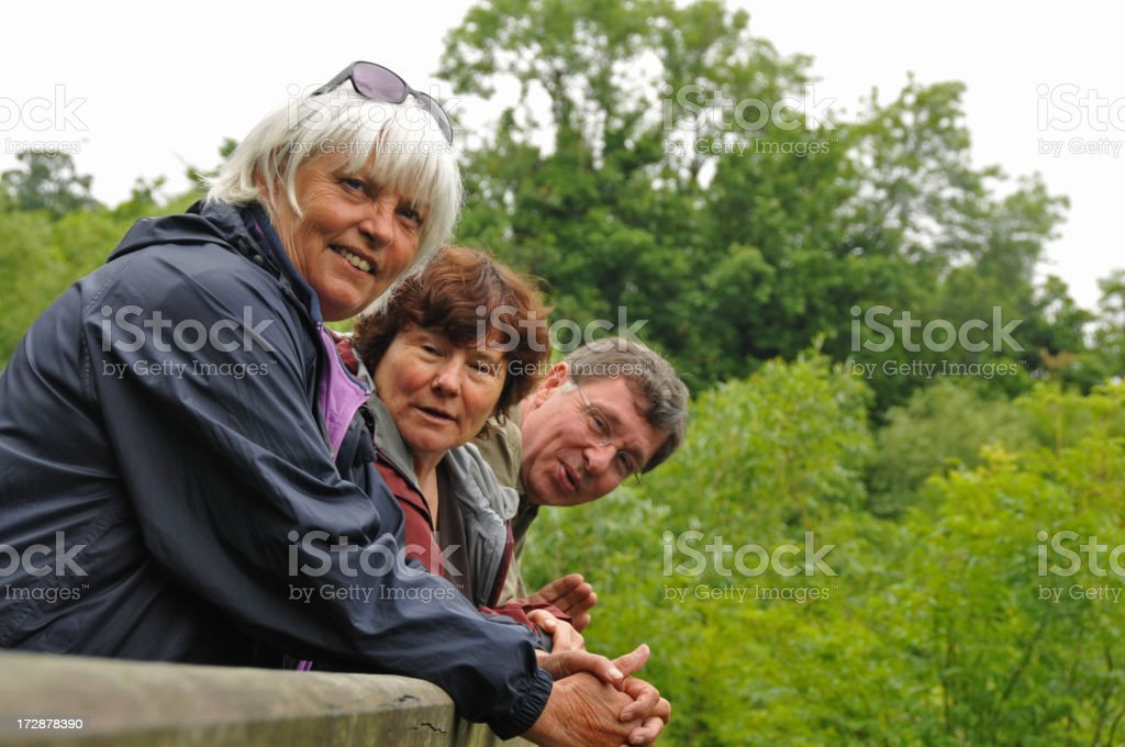 Three happy seniors leaning on a bridge royalty-free stock photo