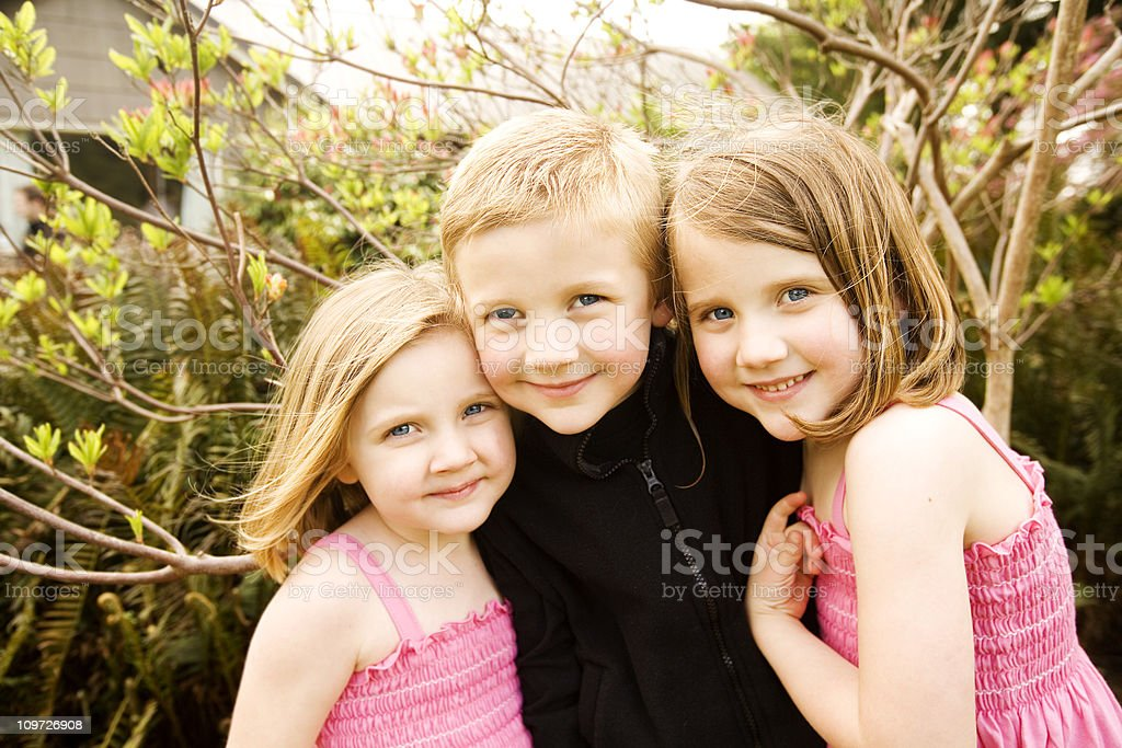Three Happy Siblings Smiling Outside, Two Little Girls, One Boy royalty-free stock photo