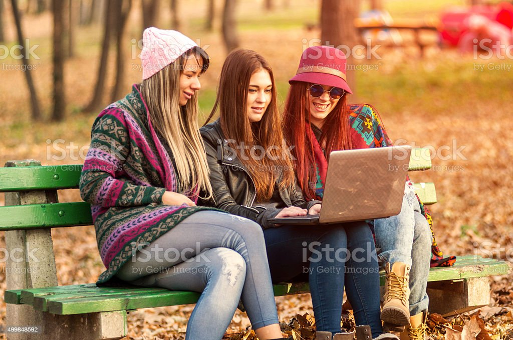 Three happy smiling female friends on laptop stock photo