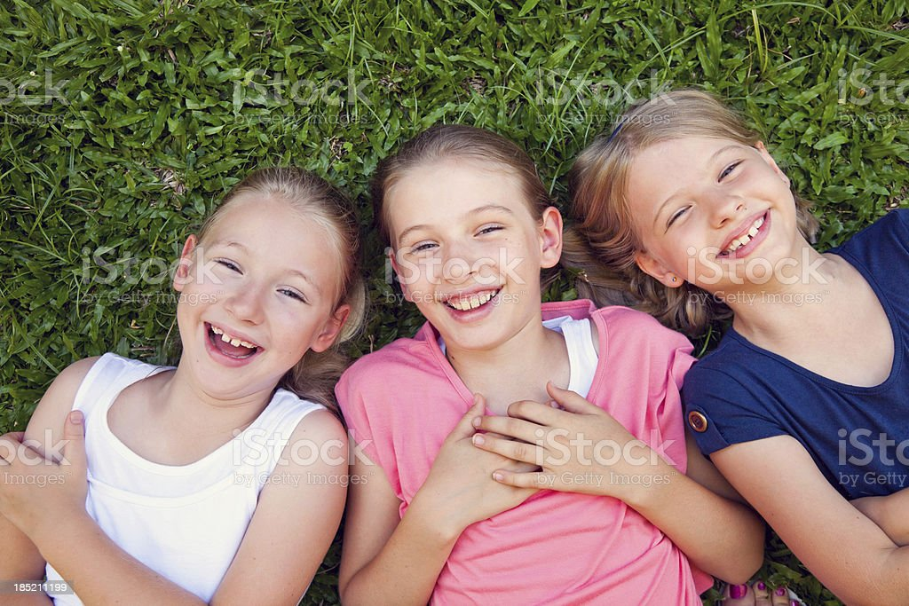 Three happy smiling laughting little girls children lying grass royalty-free stock photo