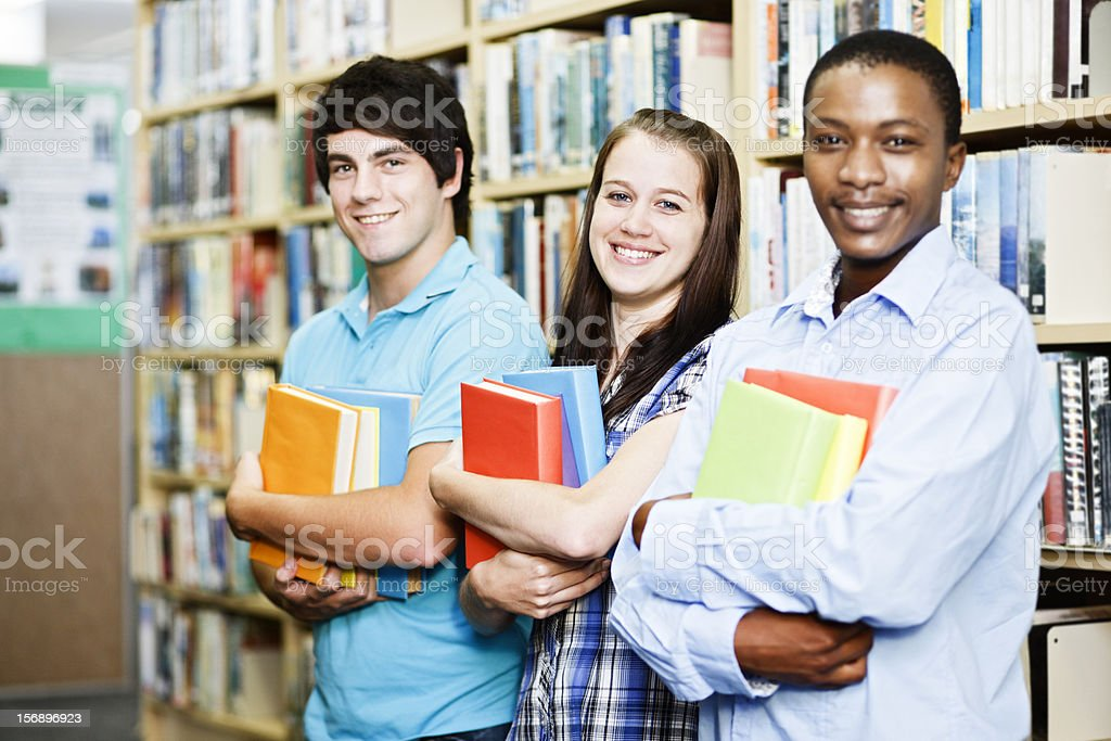 Three happy students in library with arms full of books royalty-free stock photo