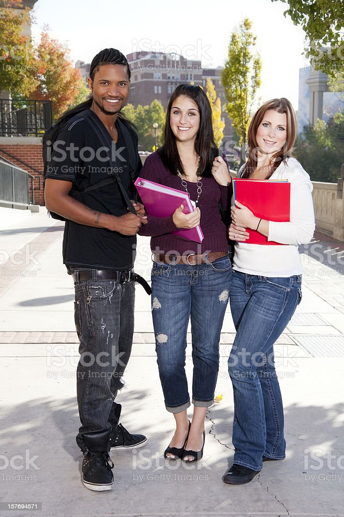 Three happy students outdoors at college campus royalty-free stock photo