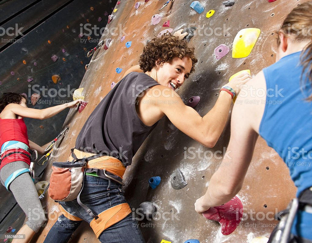 Three happy teenagers having fun at rock climbing wall stock photo