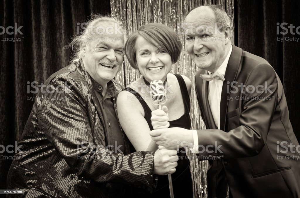 Three happy vocalists performing together on stage stock photo