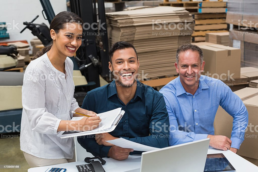 Three happy warehouse managers working together  stock photo