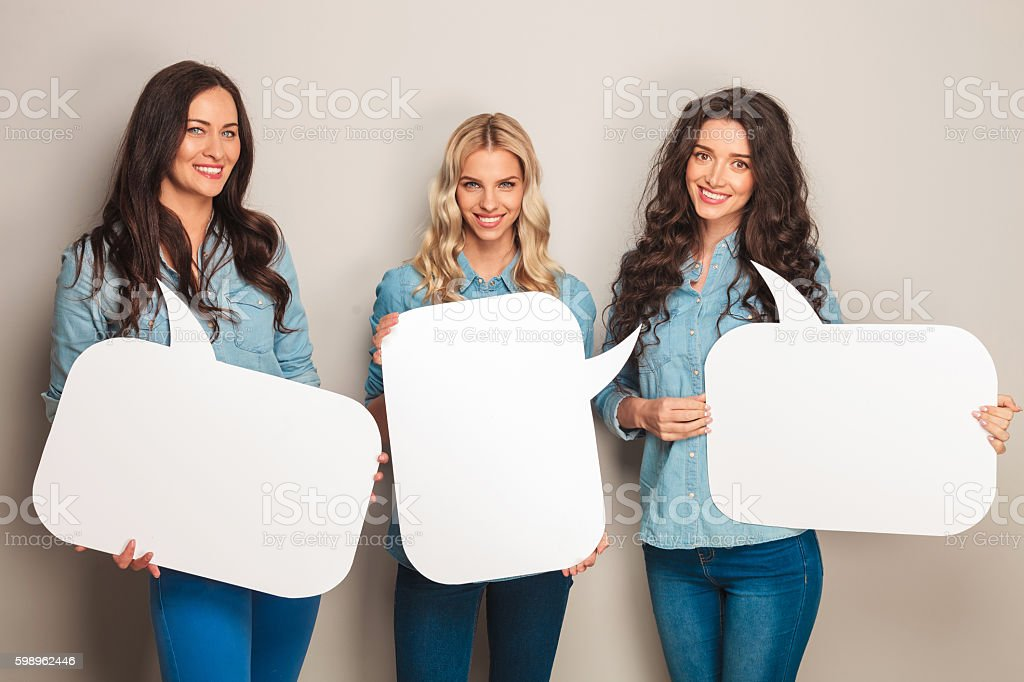 three happy women in jeans clothes holding speech bubbles stock photo
