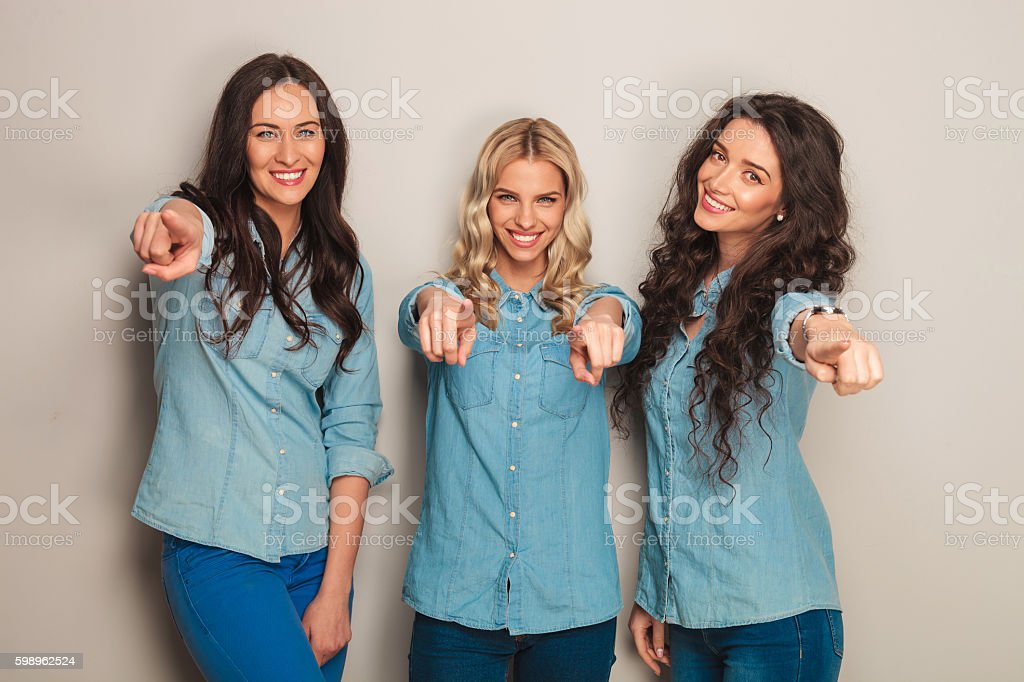 three happy women in jeans clothes pointing fingers stock photo