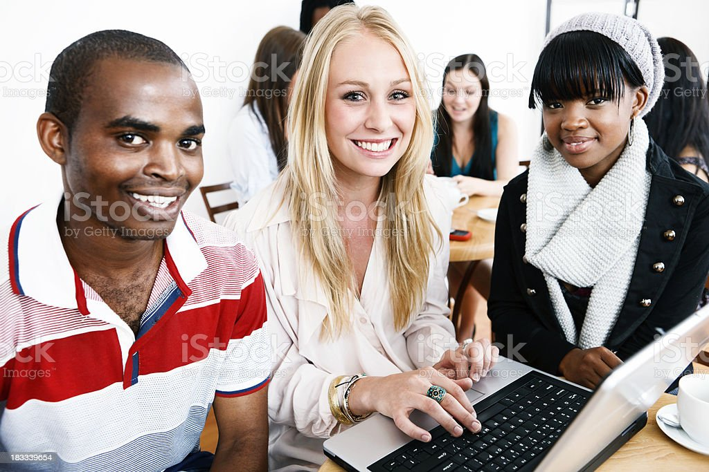Three happy young people, possibly students, round open laptop royalty-free stock photo