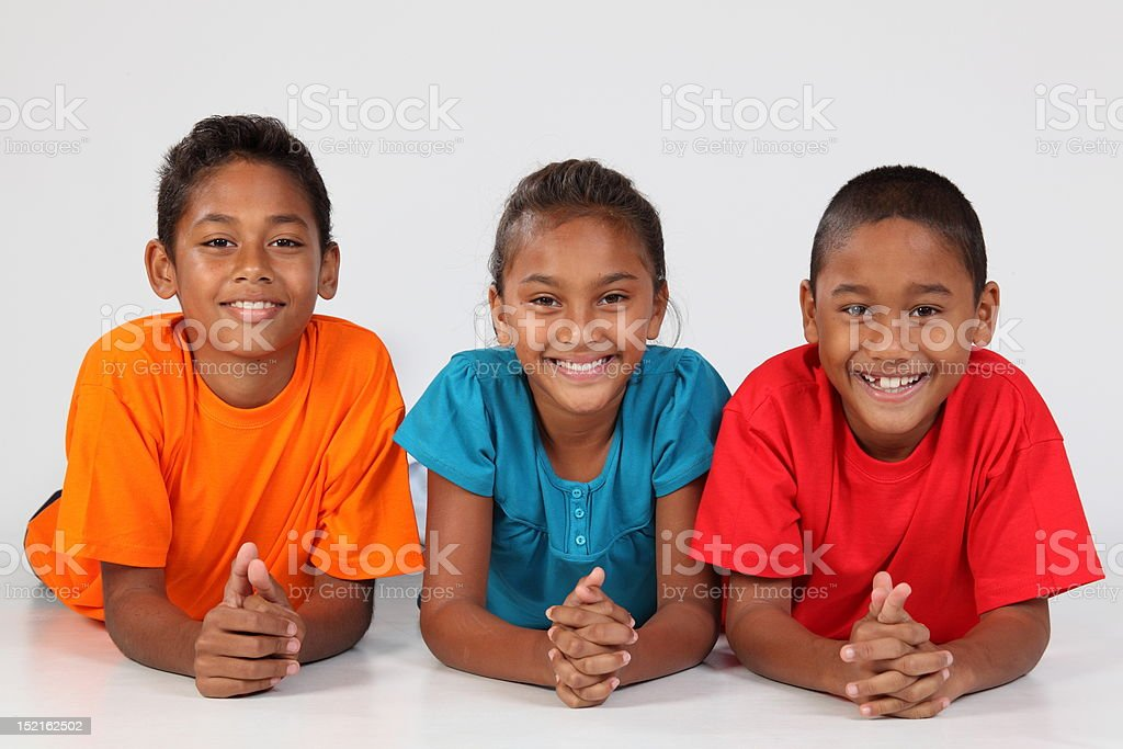 Three happy young school friends lying on floor together royalty-free stock photo