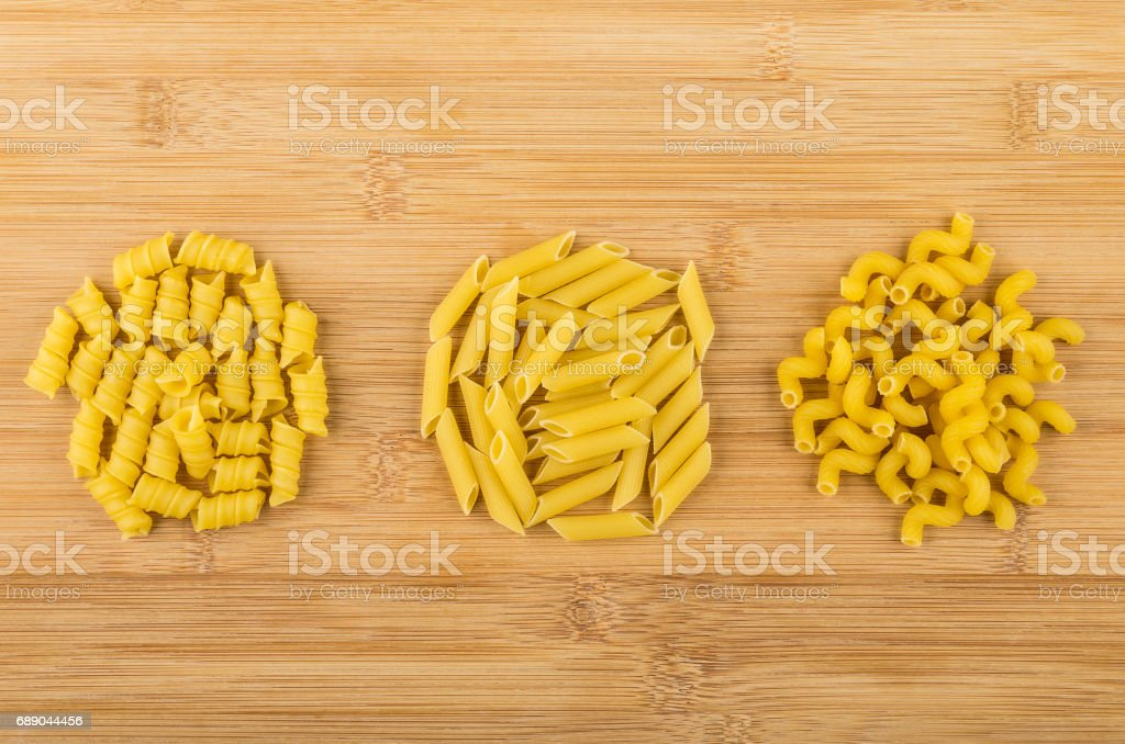 Three heap of different pasta on bamboo table stock photo