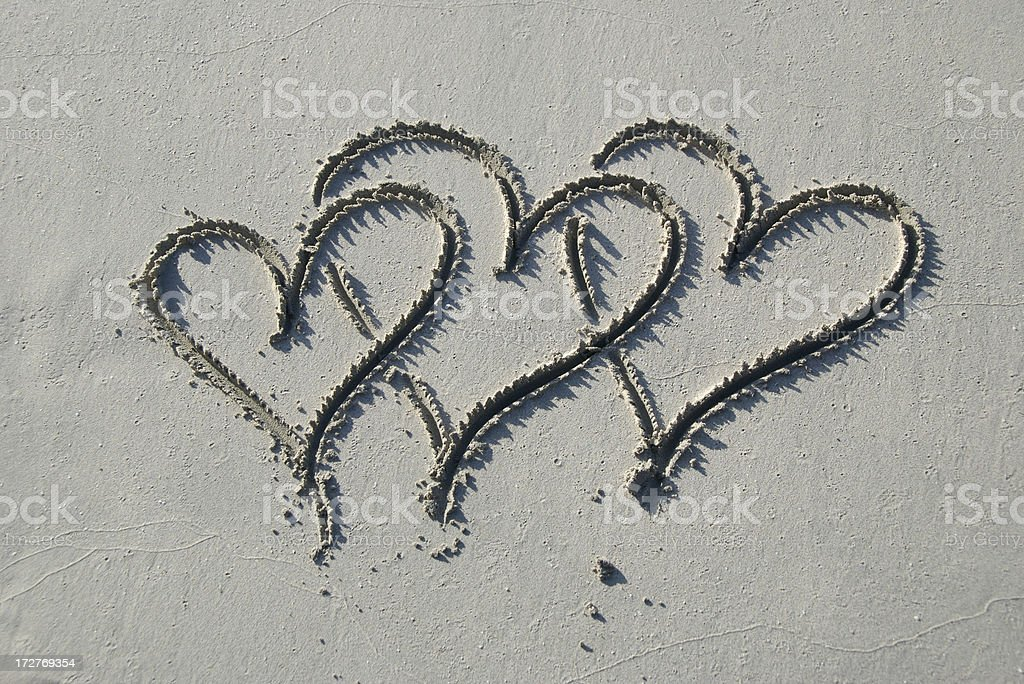 Three Hearts Drawn in Smooth Gray Sand royalty-free stock photo