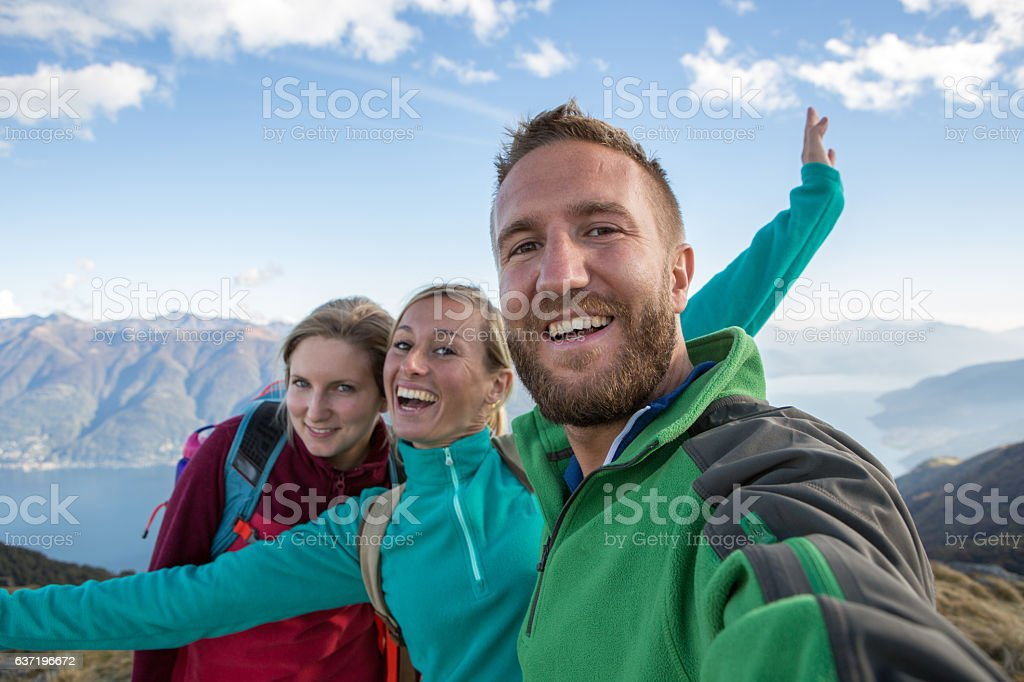 Three hikers taking selfie on mountain top stock photo