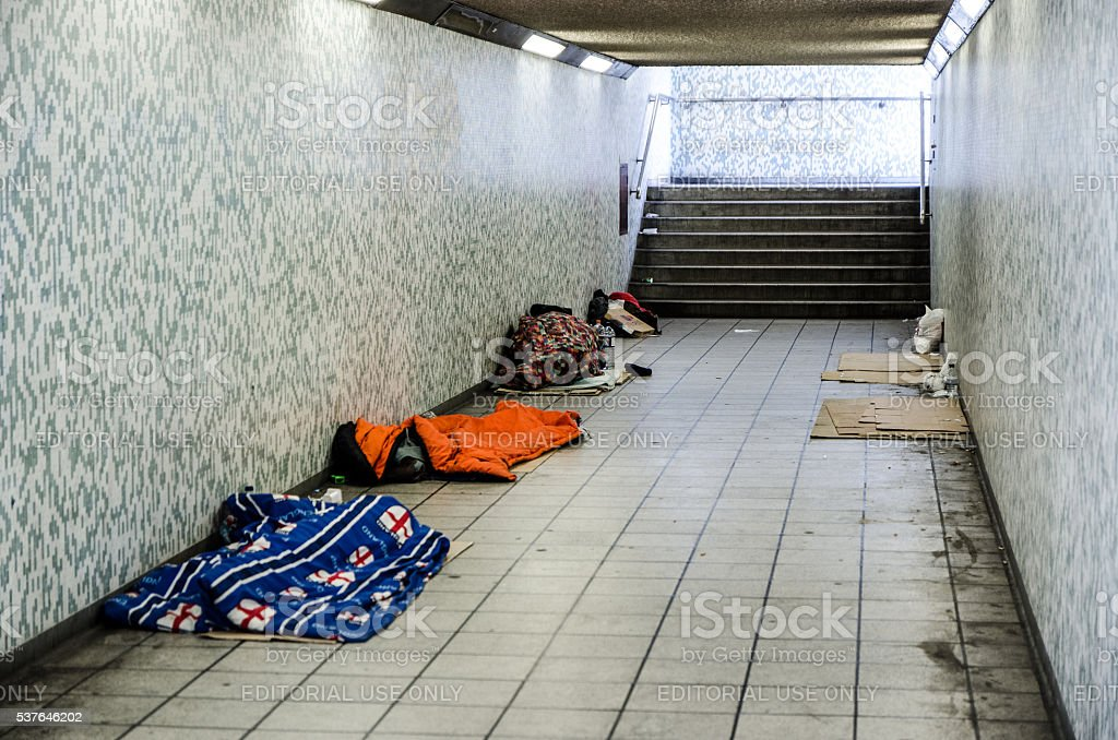 Three homeless people sleeping in sleeping bag in a tunnel with other...
