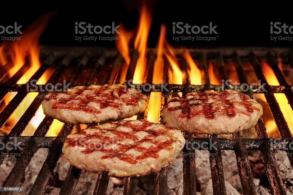 Three Homemade Browned Burgers On The Hot Flaming BBQ Grill stock photo
