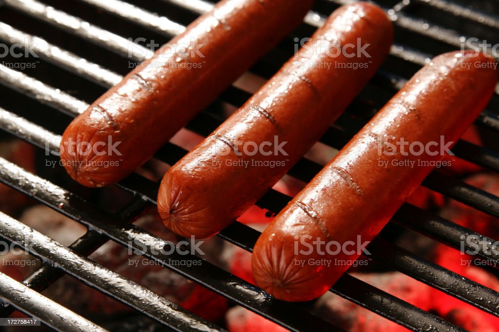 Three hot dogs on a barbecue grill with coal burning royalty-free stock photo