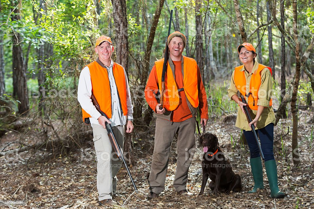 Three hunters with hunting dog stock photo