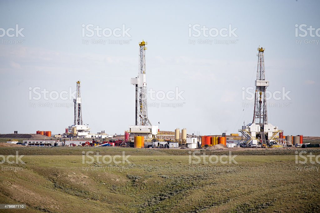 Three hydro- fracking derricks drilling natural gas on a plain stock photo