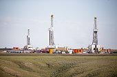 Three hydro- fracking derricks drilling natural gas on a plain