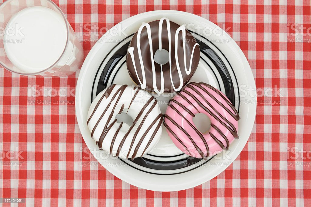 Three Iced Doughnuts and Glass of Milk, Red Checkered Tablecloth royalty-free stock photo