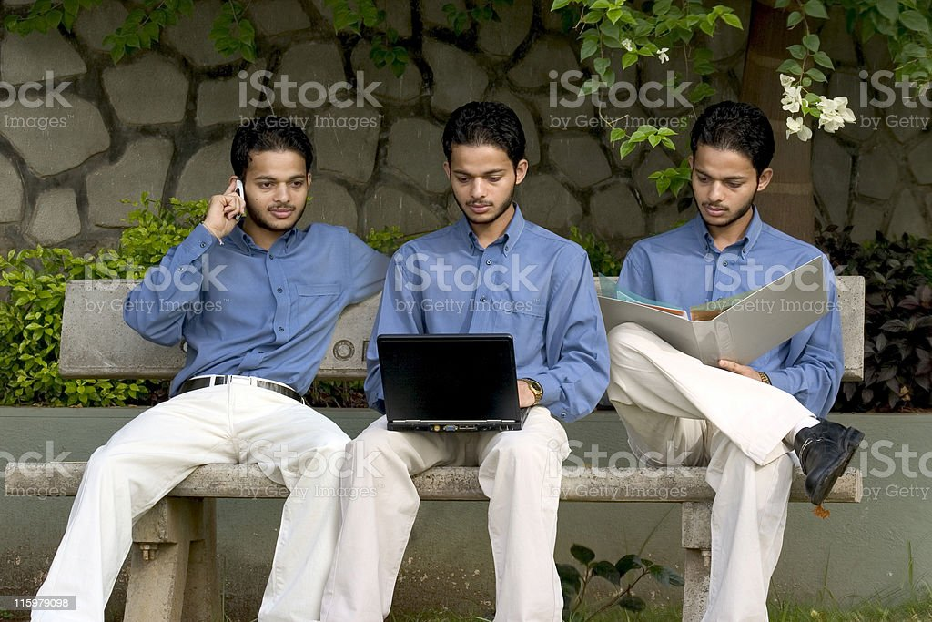 Three identical Indian Male worker Multi Tasking Laptop File Phone stock photo