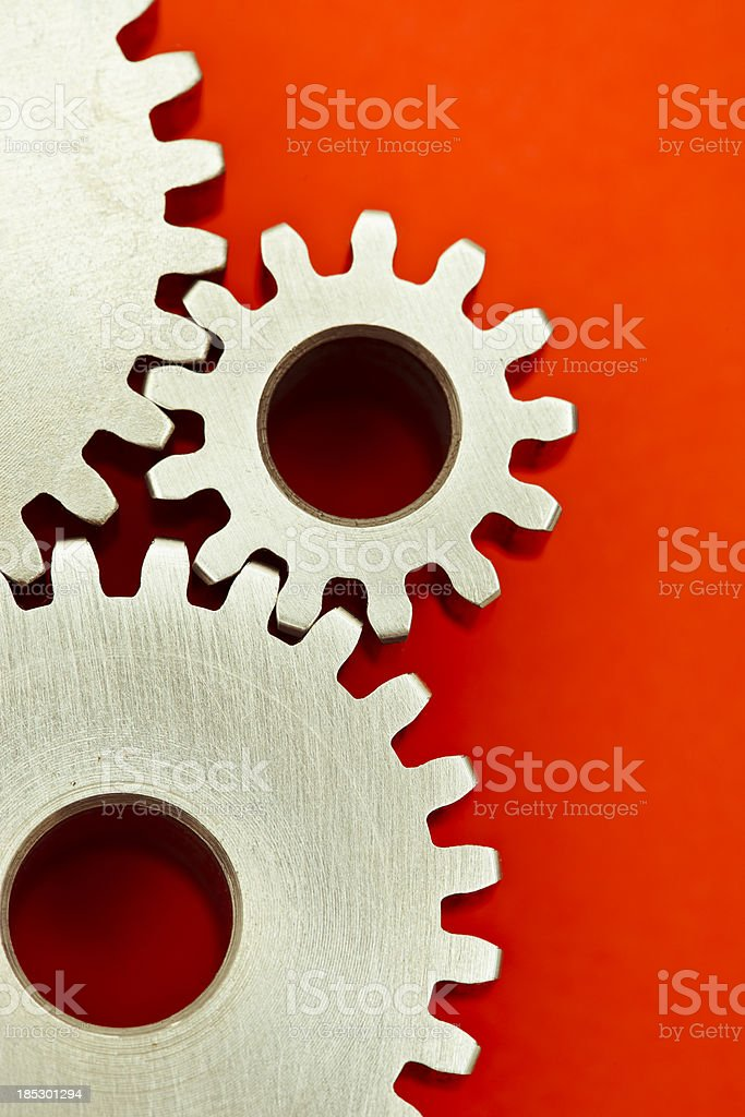 Three interlocking gears on red background royalty-free stock photo