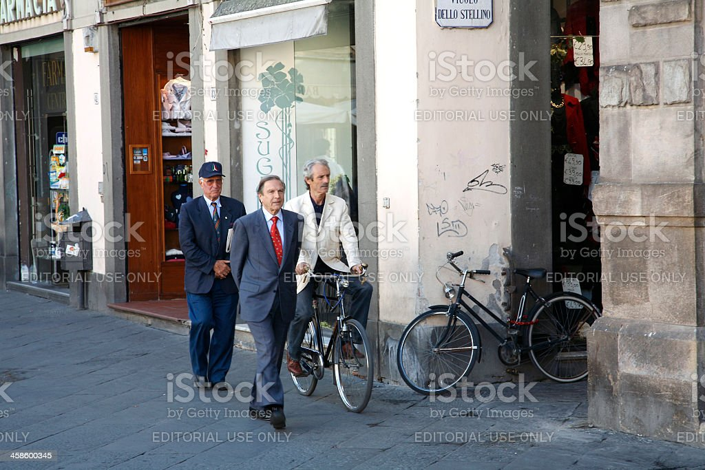 Three Italian Gentlemen Walking and Cycling To Work Lucca Tuscany royalty-free stock photo
