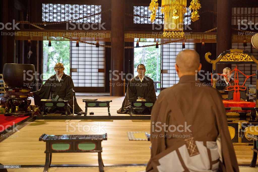 Three Japanese monks in prayer inside a Buddhist Temple stock photo