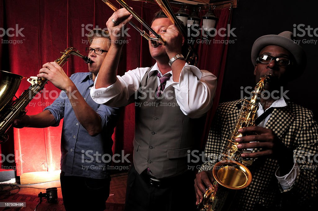 Three jazz musicians playing music with red curtain in back stock photo