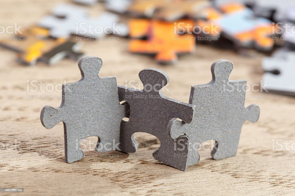 Three jigsaw puzzle pieces on a table joint together. Shallow depth...