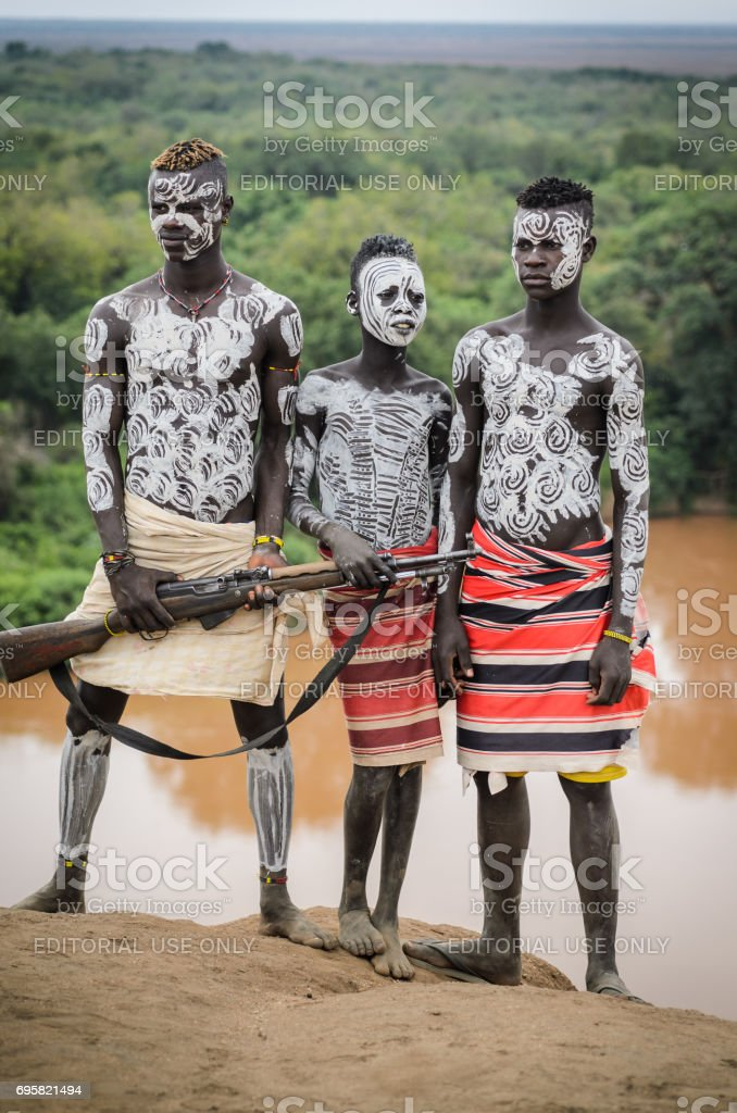 three Karo boys on the banks of Omo river, Ethiopia stock photo