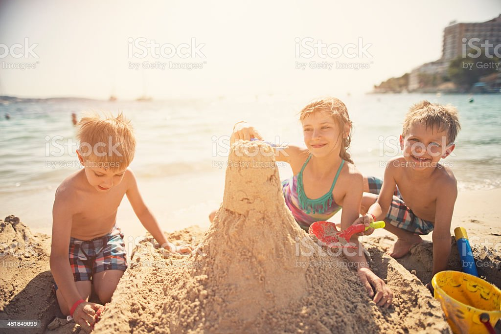 Three kids building a sandcastle stock photo