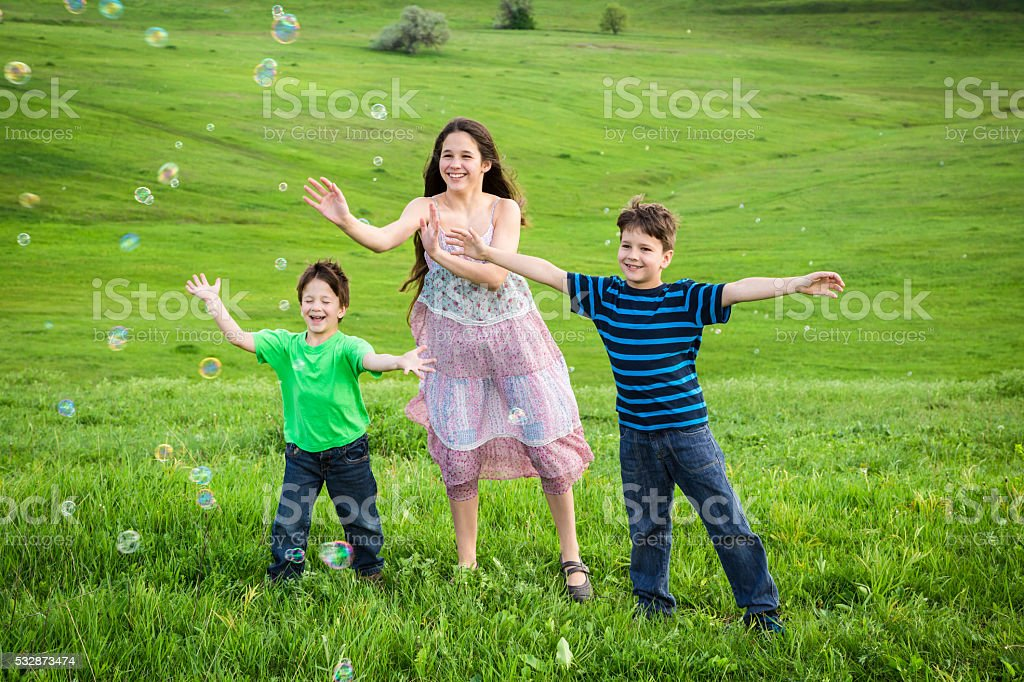 Three kids catch the soap bubbles on lawn stock photo