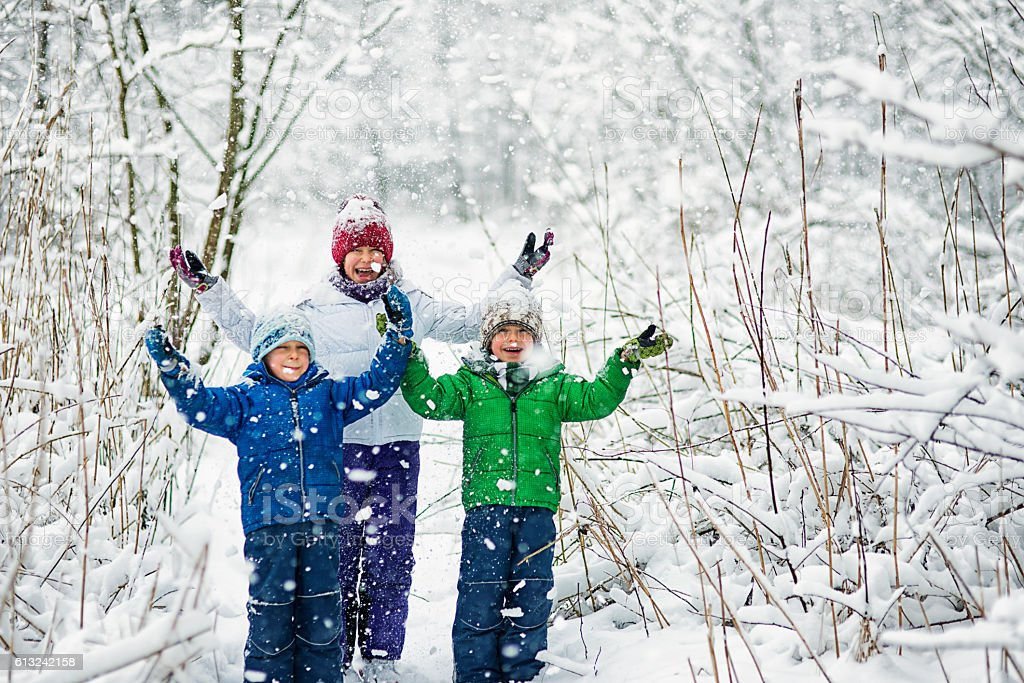Three kids enjoying first snow. stock photo