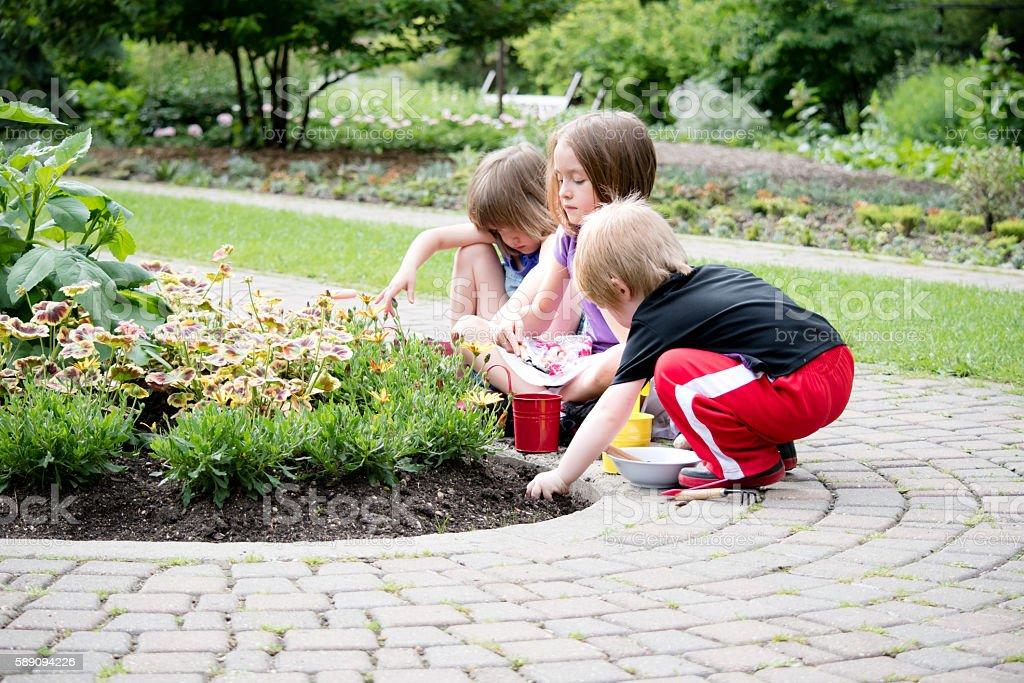 three kids gardening together stock photo
