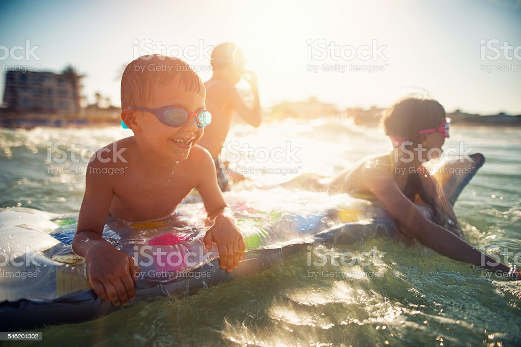 Three kids having fun in sea on air bed stock photo