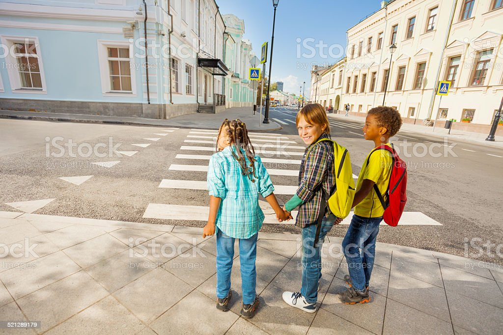 Three kids holding hands stand on street stock photo