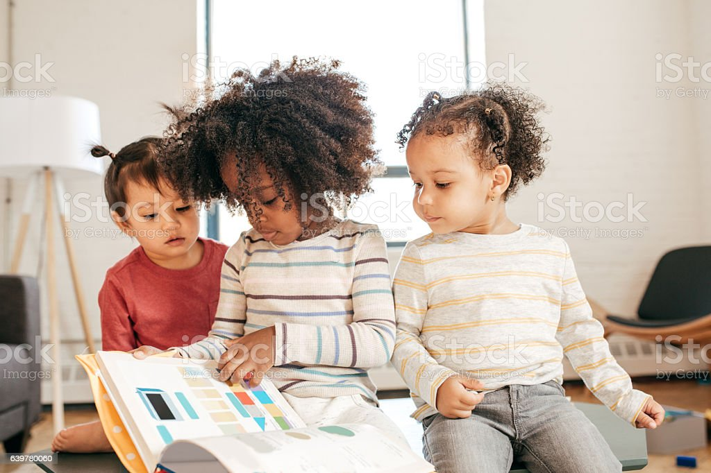 Three kids in daycare with book stock photo
