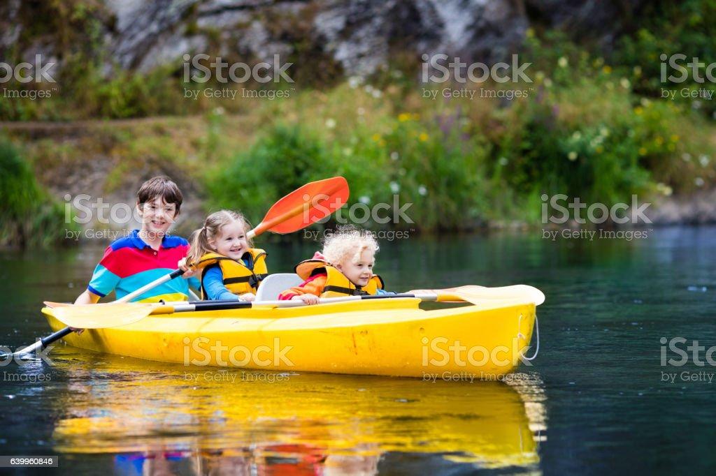 Three kids kayaking on a river stock photo